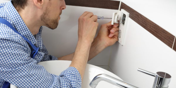 Elektriker Handwerker beim Wechseln einer Steckdose im Bad